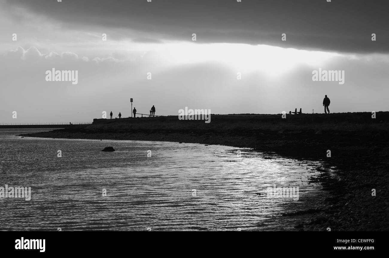 A shot of people walking along the coastline of Galway Bay towards the sun breaking through the clouds creating - Stock Image