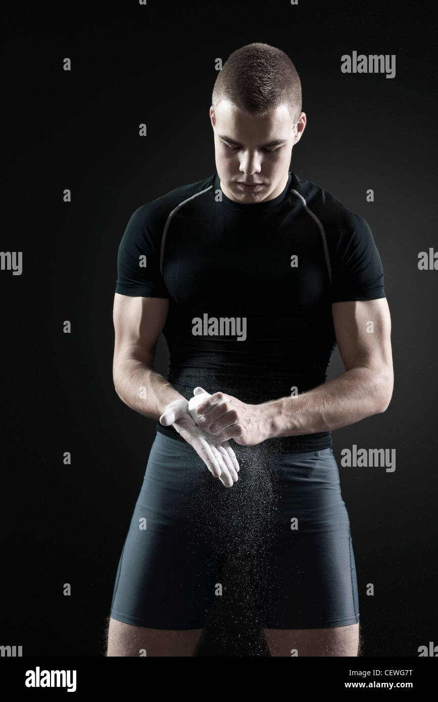 Male athlete applying chalk to hands - Stock Image