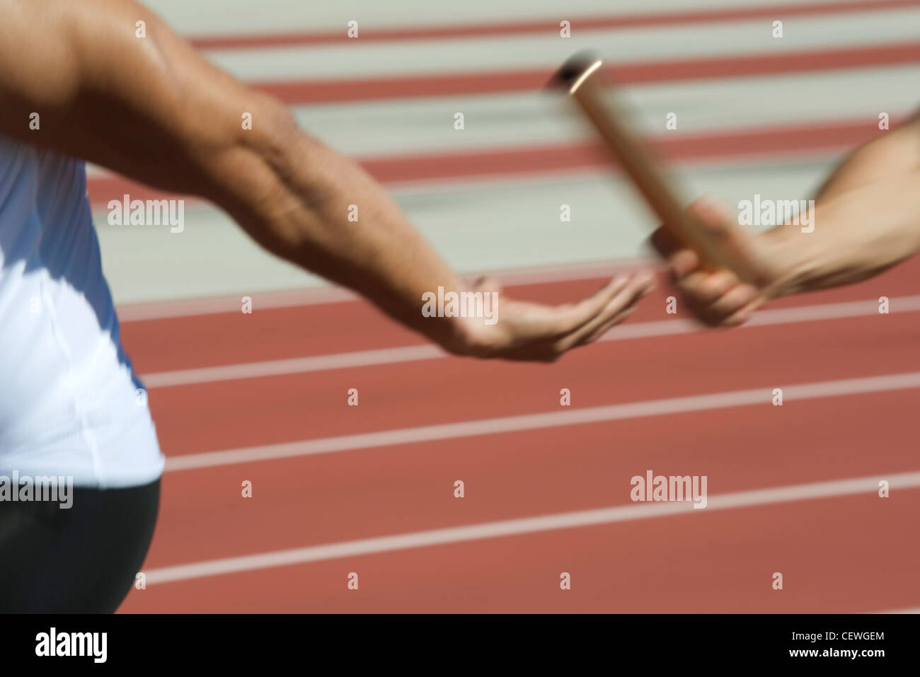 Runners exchanging baton in relay race, cropped - Stock Image