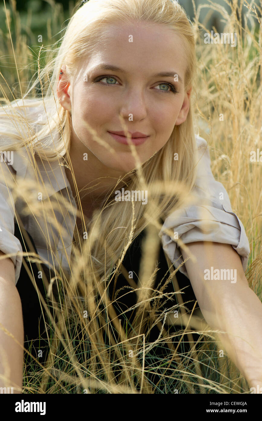 Young woman relaxing in tall grass, portrait - Stock Image