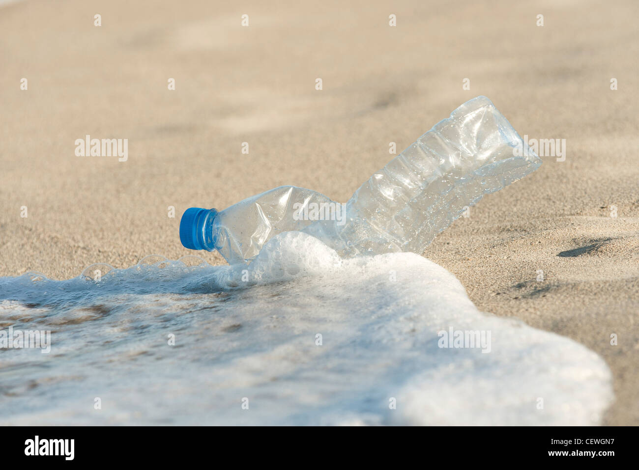 Abandonded plastic bottle on beach - Stock Image