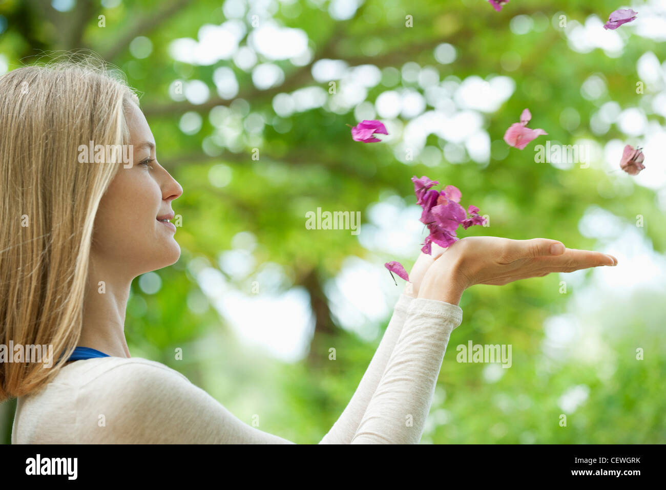 Young woman catching falling petals, side view - Stock Image