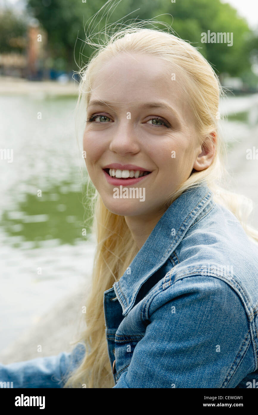 Young woman smiling, portrait - Stock Image