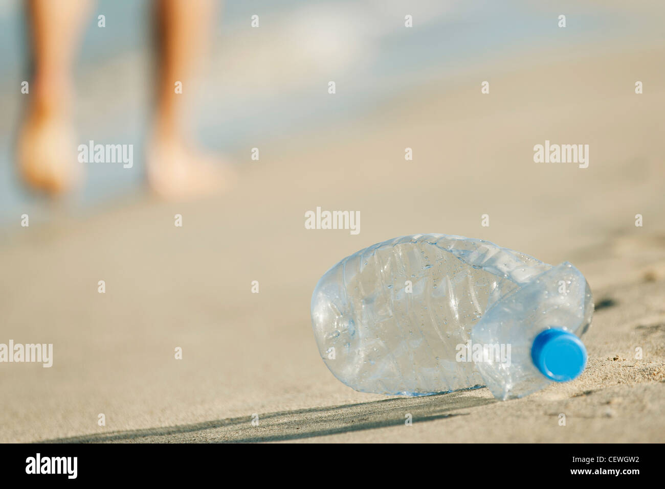 Abandoned plastic water bottle on beach - Stock Image