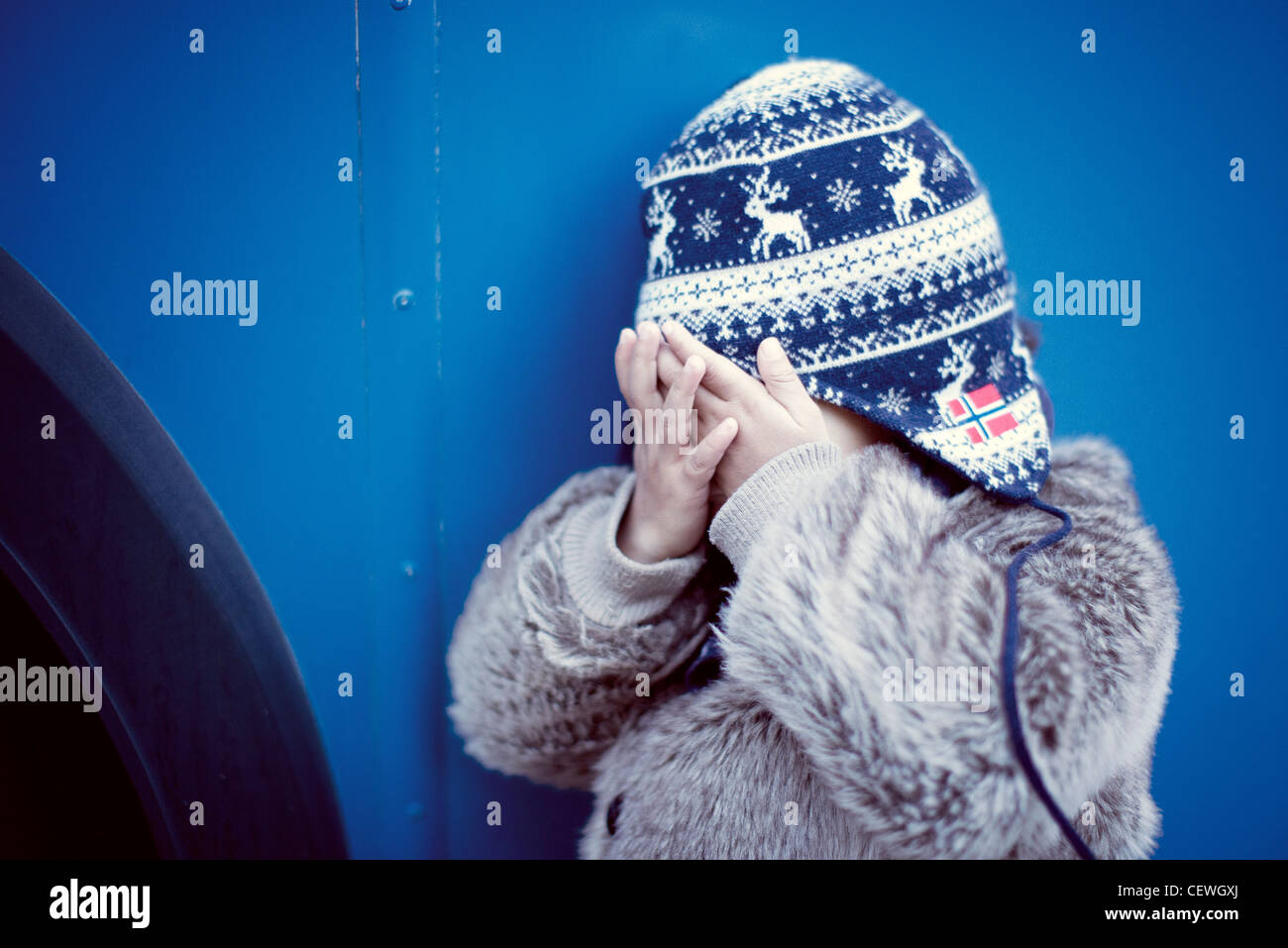 Little girl covering face with hands - Stock Image