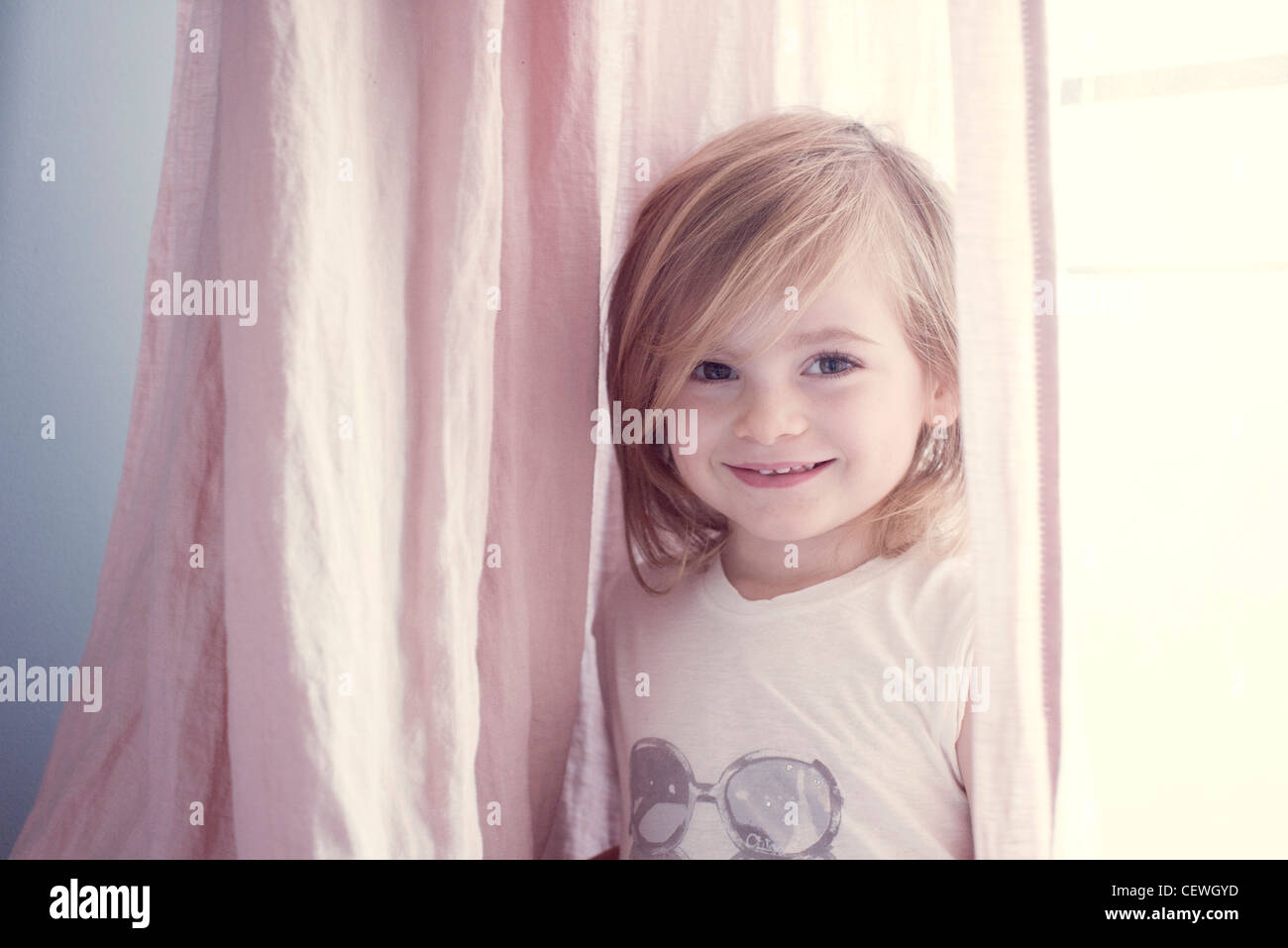 Little girl in front of window, smiling, portrait - Stock Image