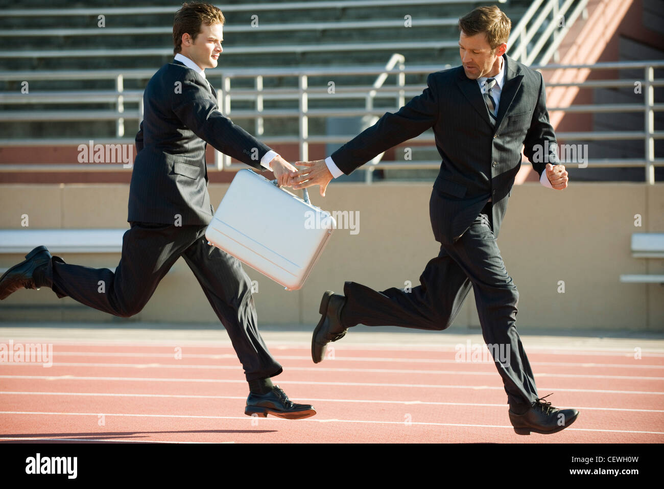 Businessmen handing off briefcase in relay race - Stock Image