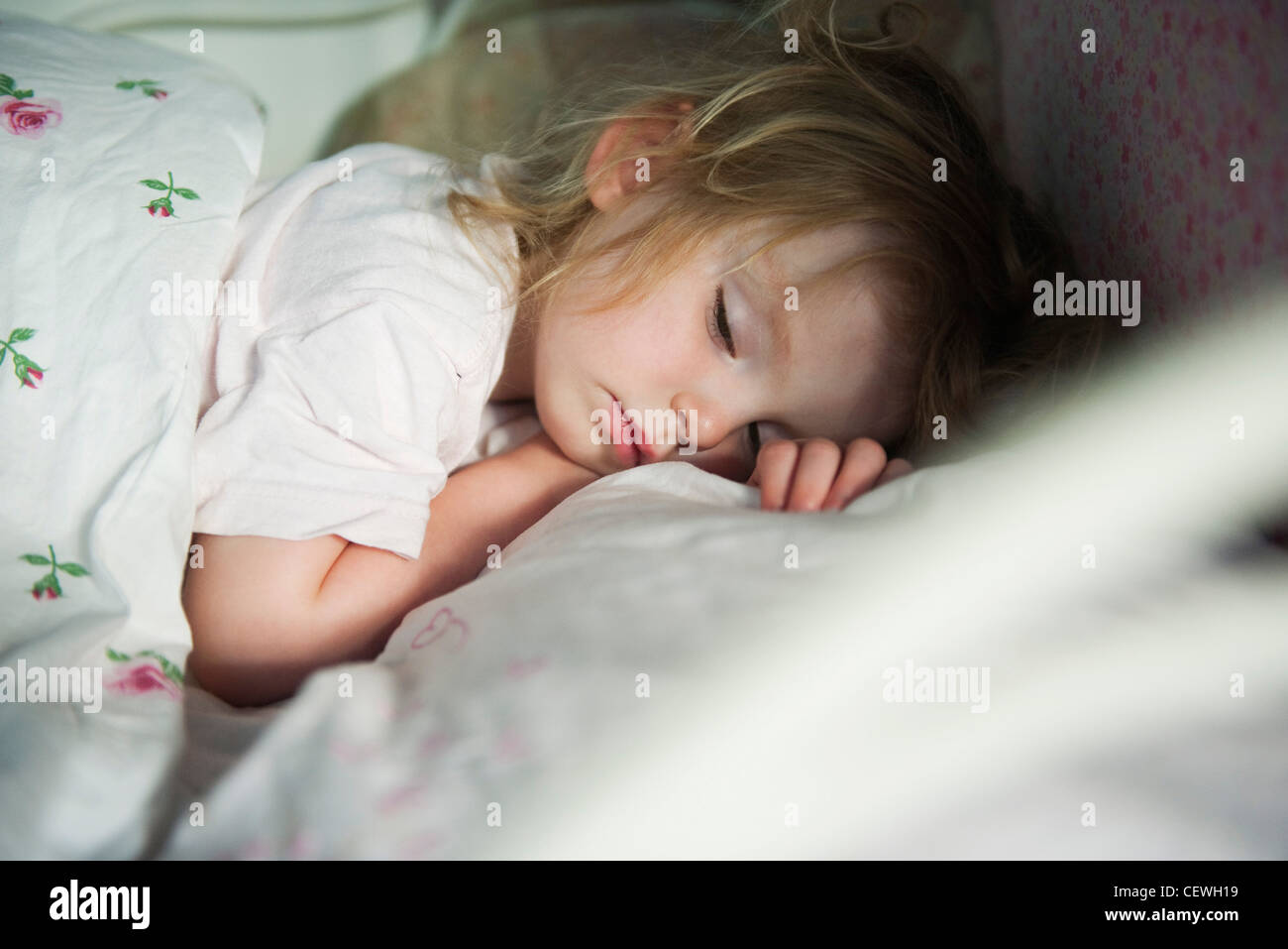 Toddler sleeping in bed - Stock Image