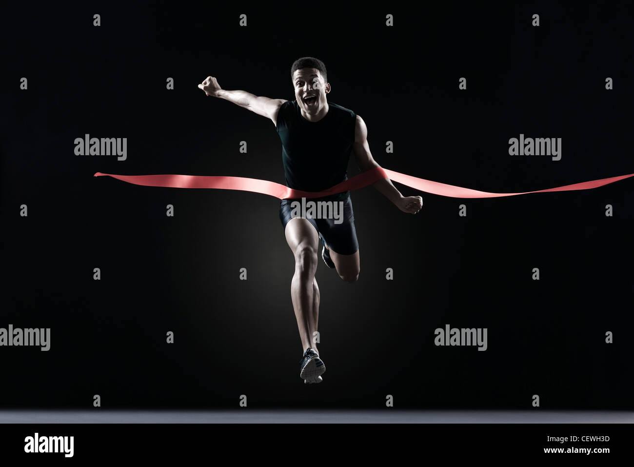 Runner crossing finish line - Stock Image