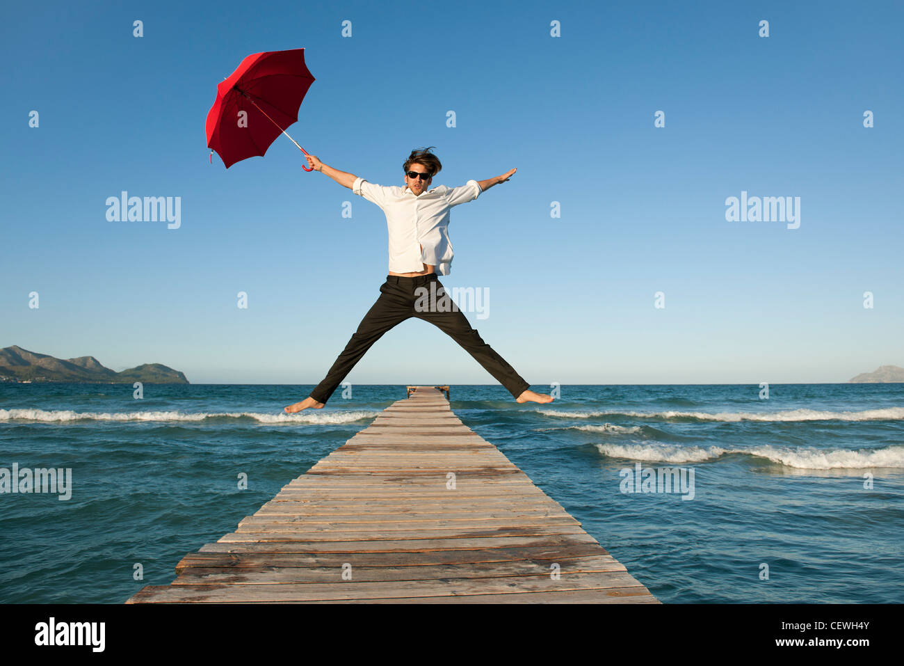 Young man jumping on pier with umbrella Stock Photo