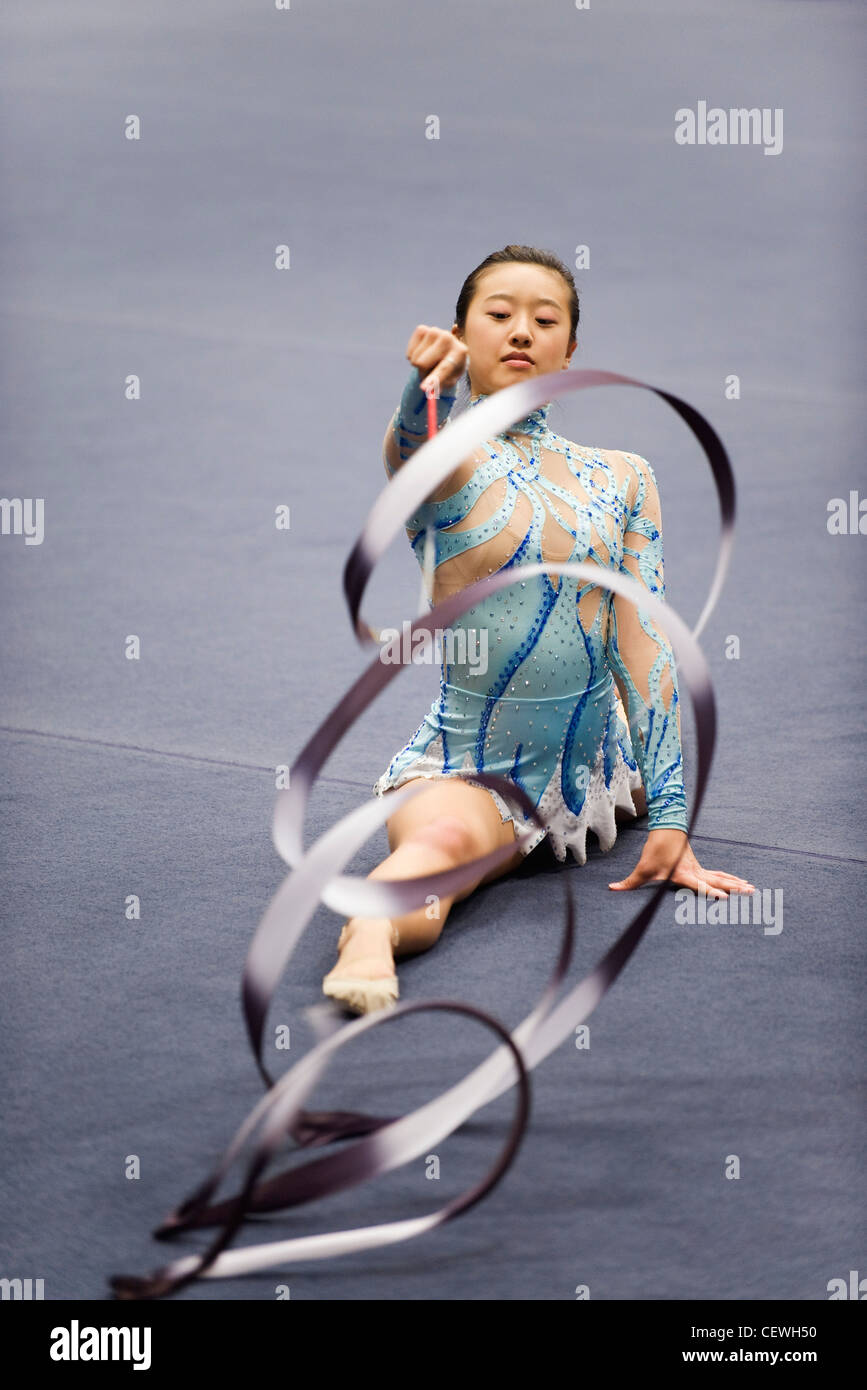 Female gymnast performing floor routine with ribbon - Stock Image