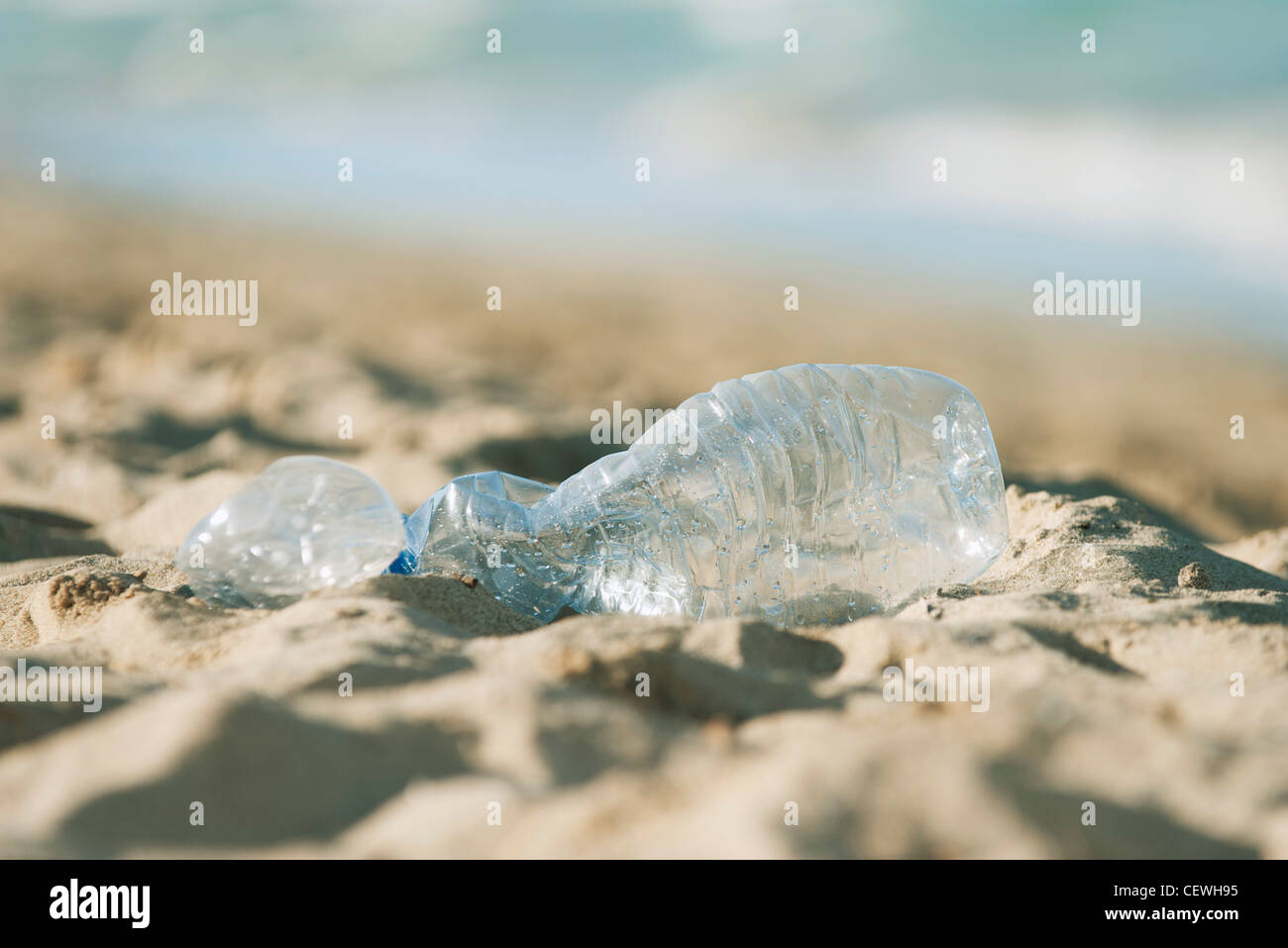 Empty plastic bottle on beach, selective focus - Stock Image