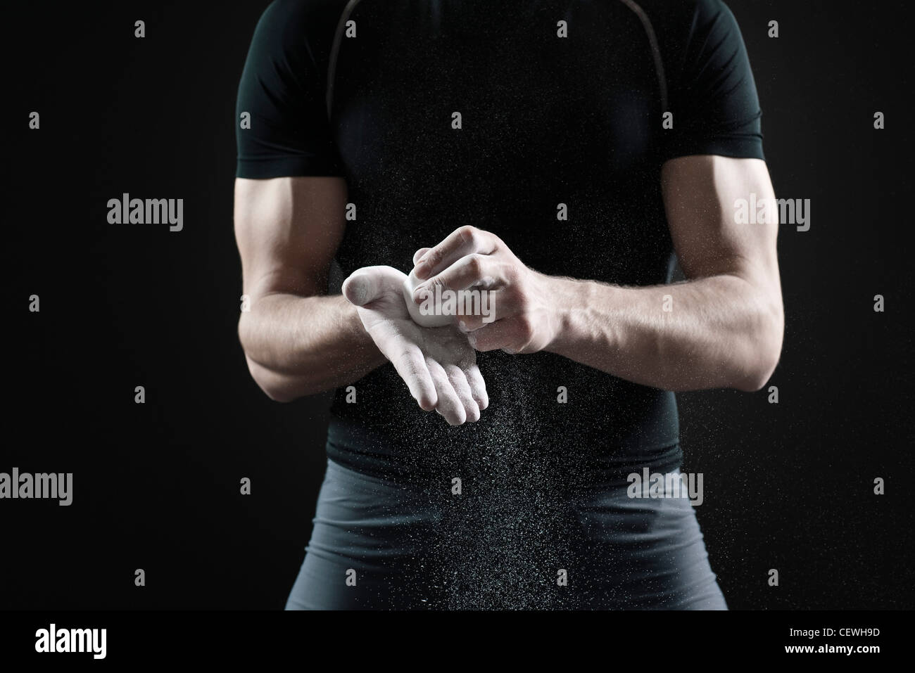 Male athlete applying chalk to hands, mid section - Stock Image