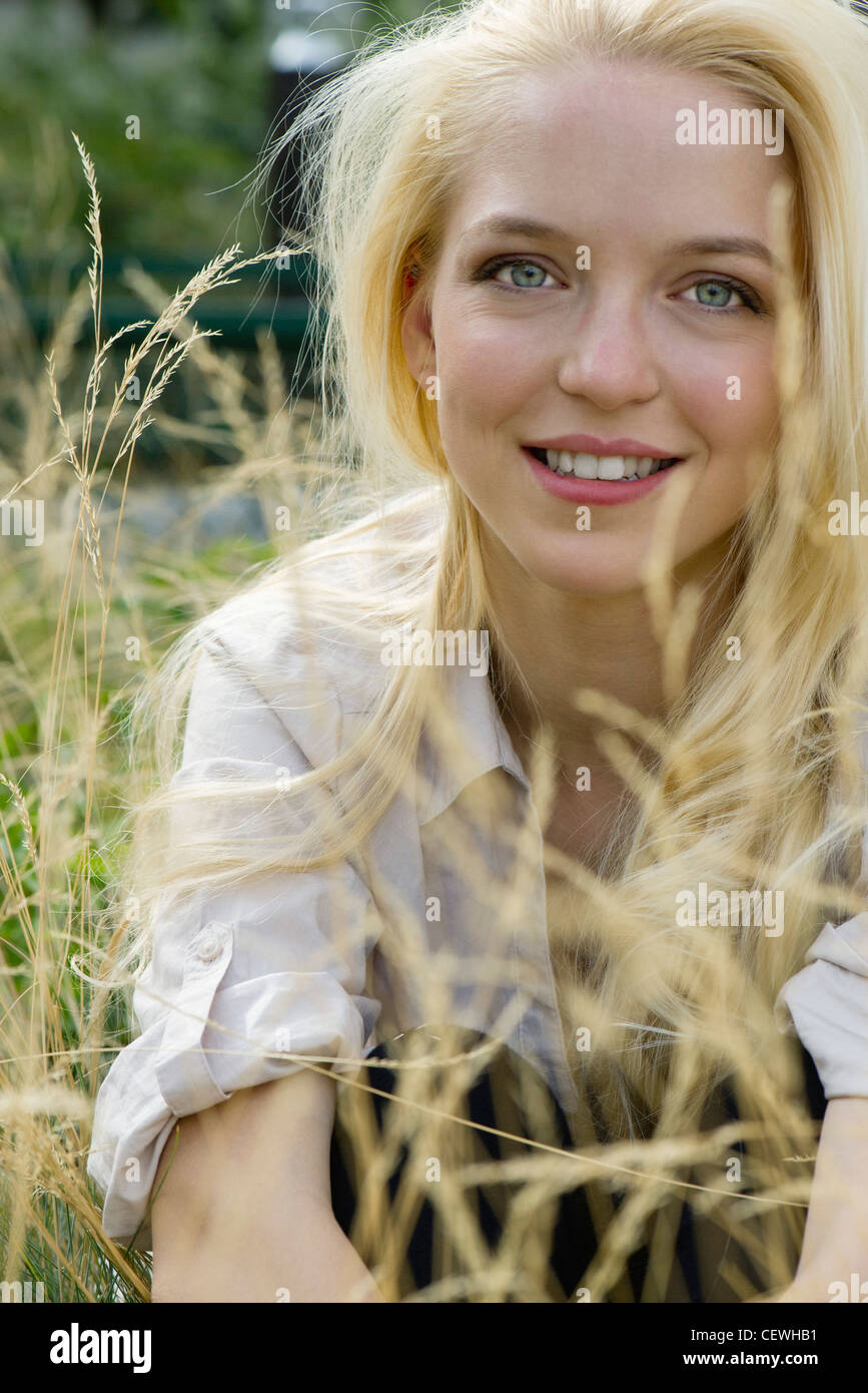 Young woman sitting in tall grass, portrait - Stock Image
