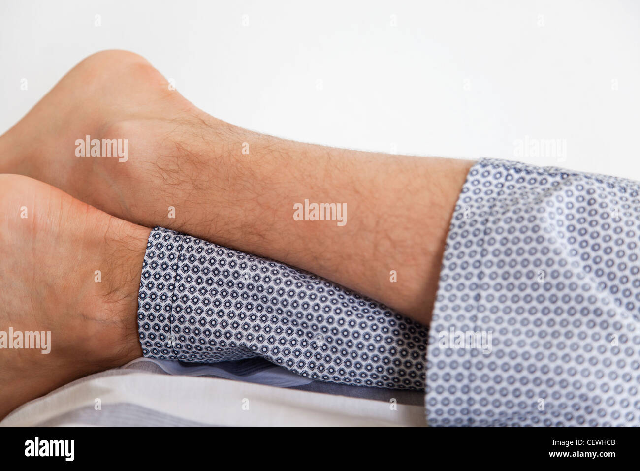 Man's leg's crossed at ankle - Stock Image