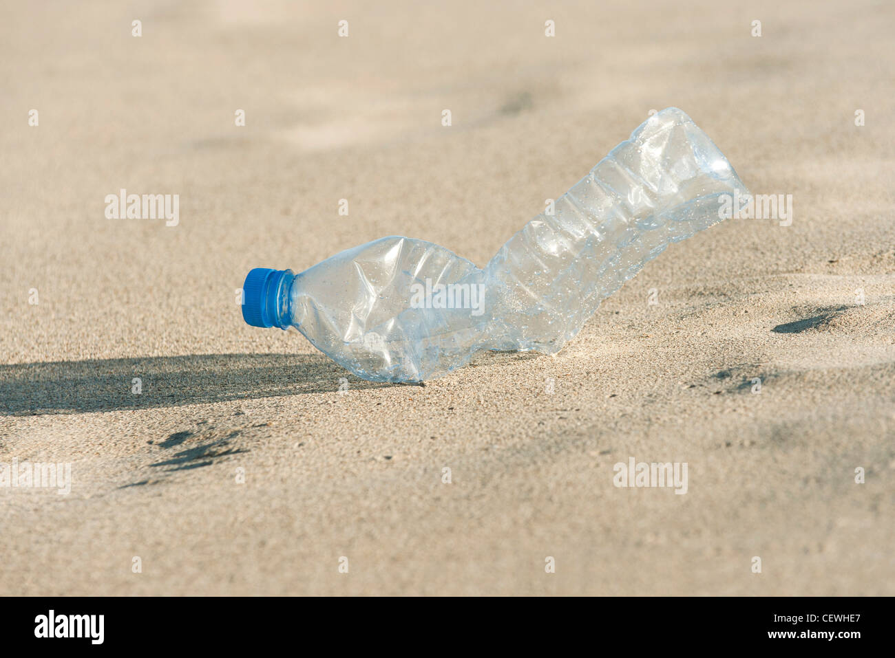 Empty plastic bottle on beach, close-up - Stock Image