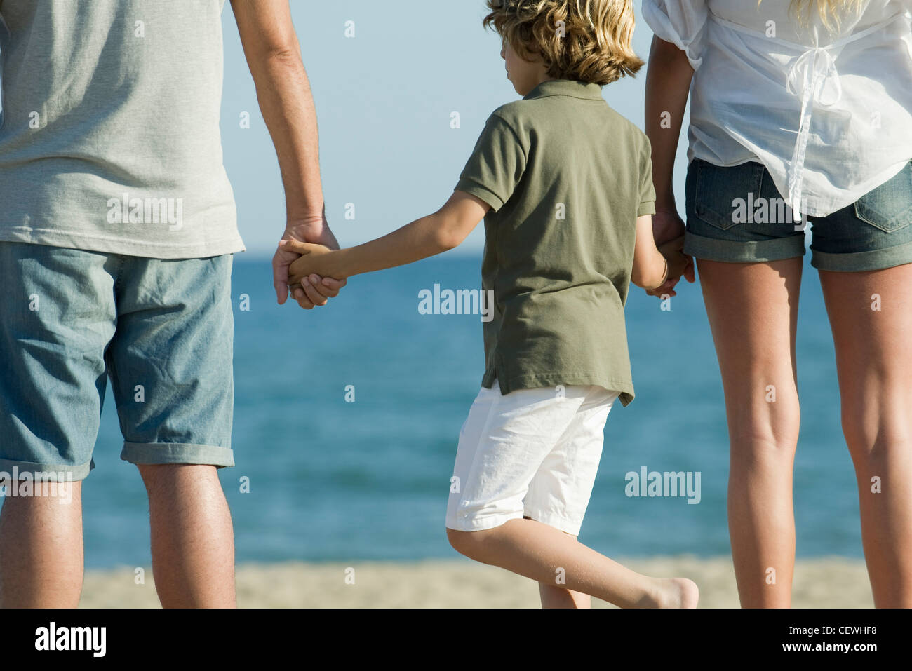 Boy holding parents' hands at the beach, rear view - Stock Image