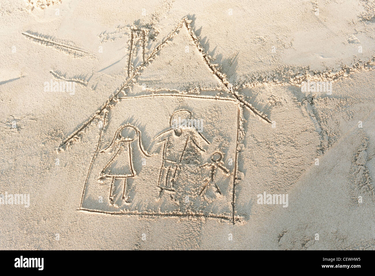 Drawing of family in house in sand, high angle view - Stock Image