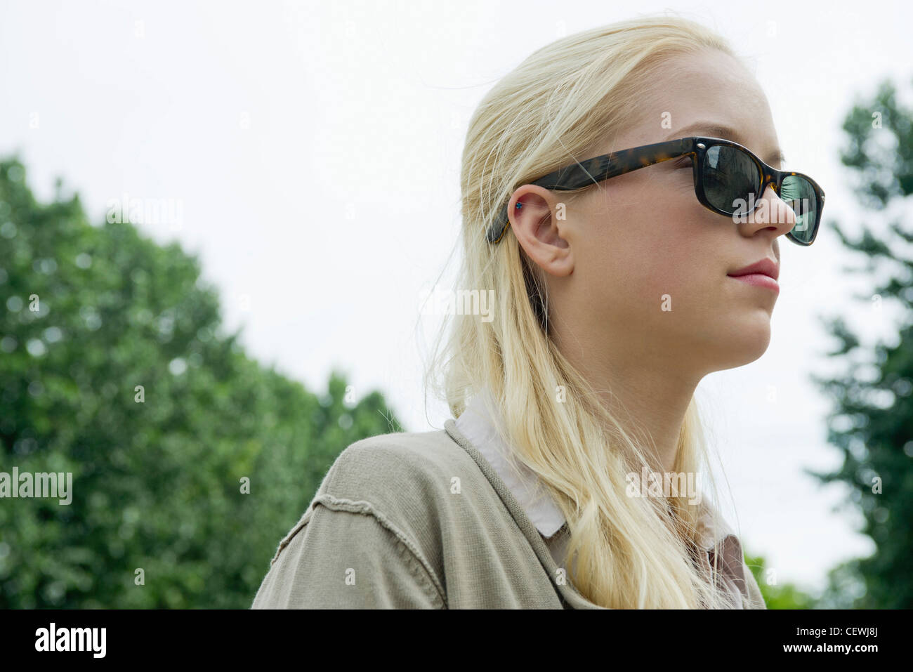 Young woman wearing sunglasses, looking away in thought - Stock Image