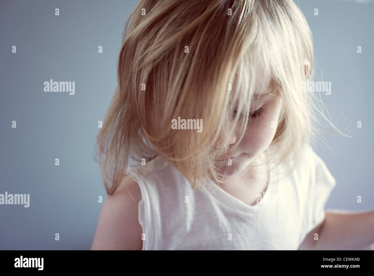 Little girl looking down, hair covering face - Stock Image