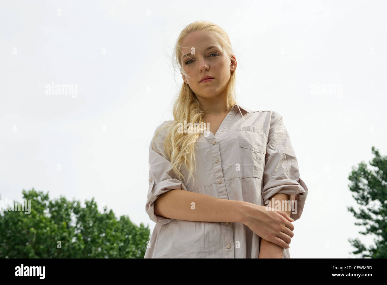 Young woman looking at camera with sad expression - Stock Image