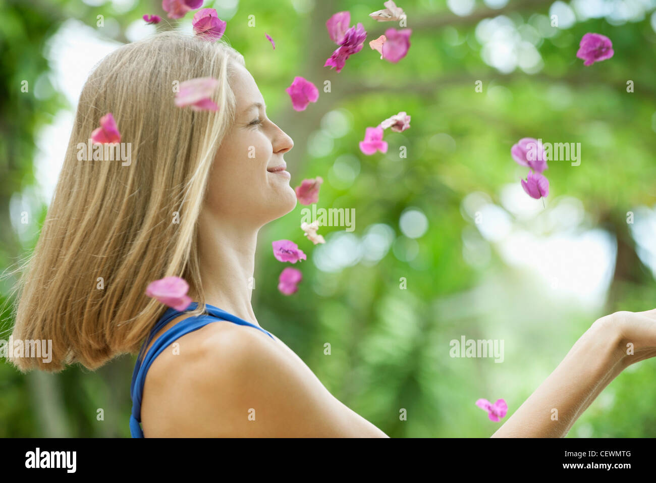 Young woman throwing petals in air, side view - Stock Image
