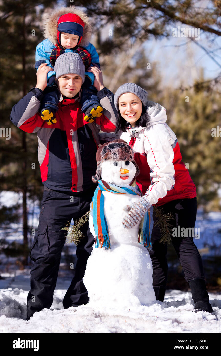 happy family: mother, father and son making a snowman outdoor on a warm winter day (focus on the woman) - Stock Image