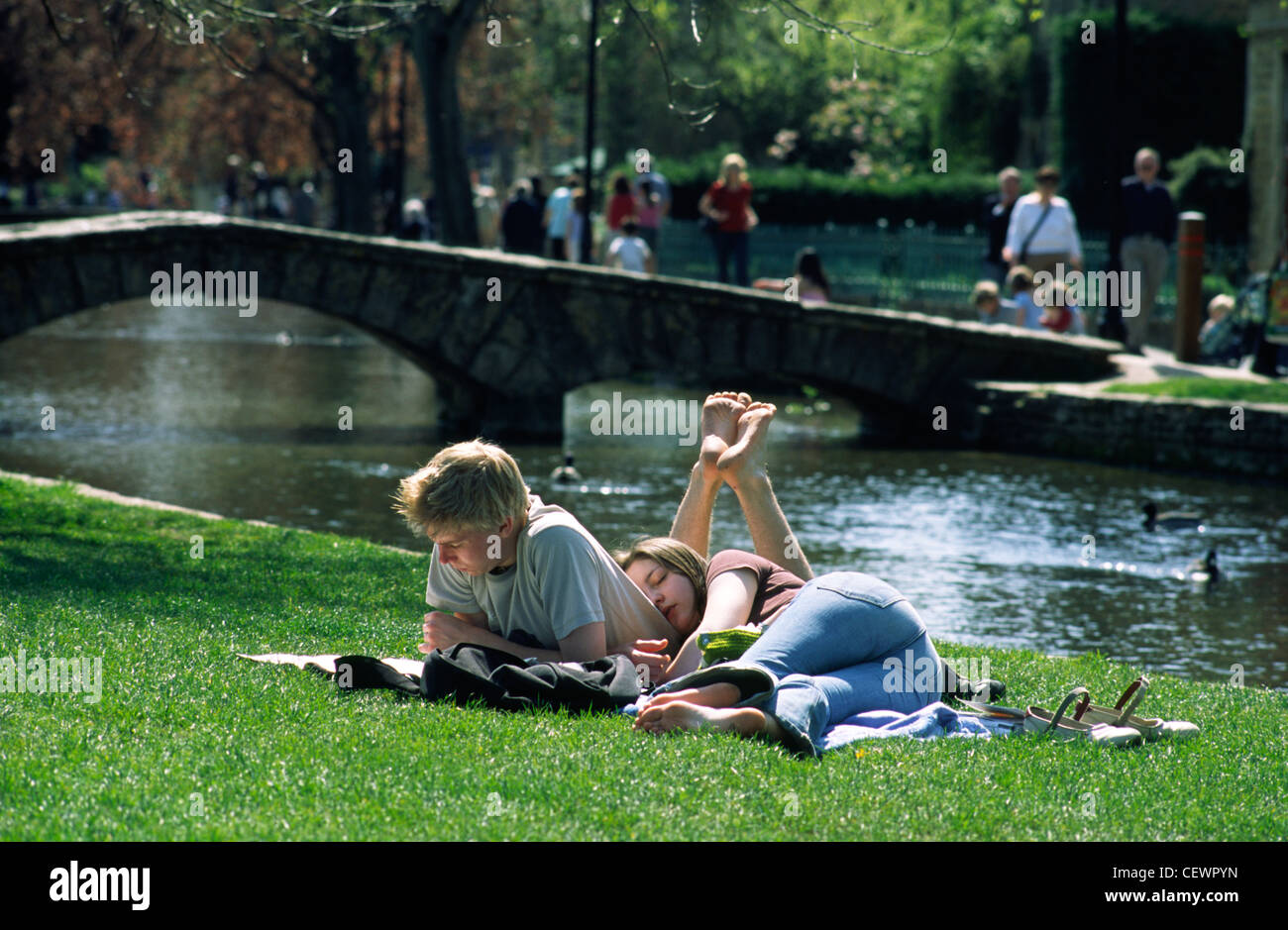 Lazy days on the riverbank at Bourton-on-the-Water in the Cotswolds. - Stock Image