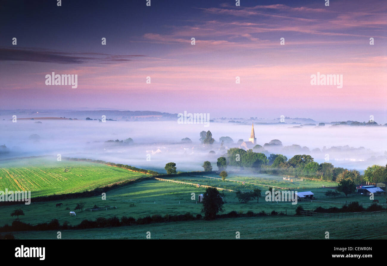 The first rays of late summer sun strike the mist covered village of Trellech. - Stock Image