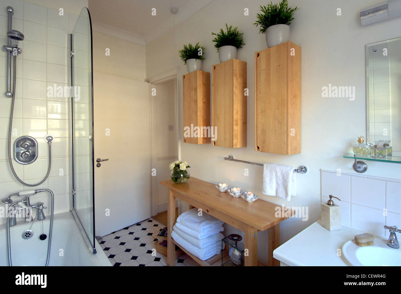 Chelsea Appartment Bathroom Interiwith White Tiled Walls, Tiled Floor, Wall  Cabinets Potted Plants On Top And Shower Above