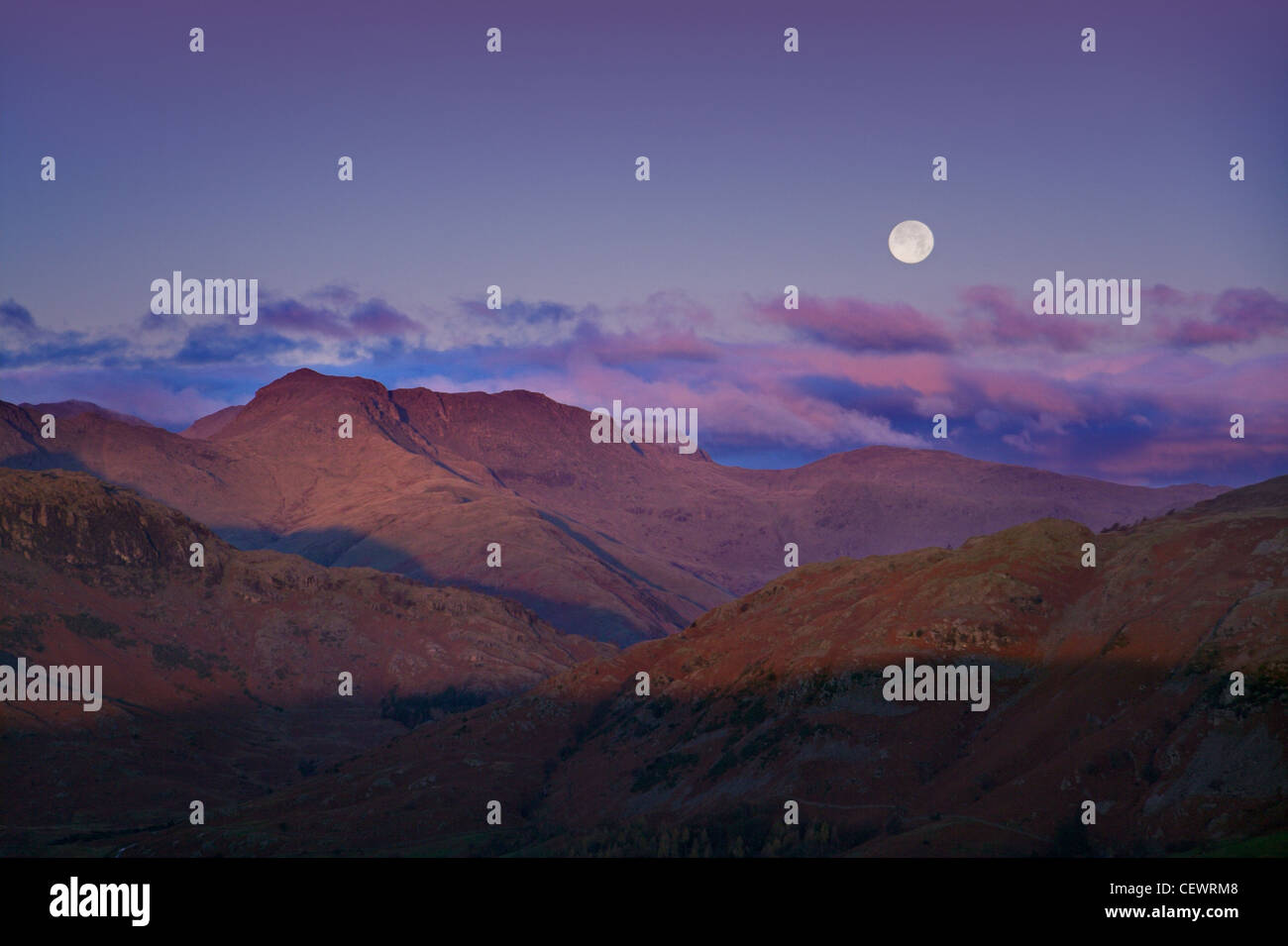 Full moon rises above the distinctive Langdale Pikes. - Stock Image