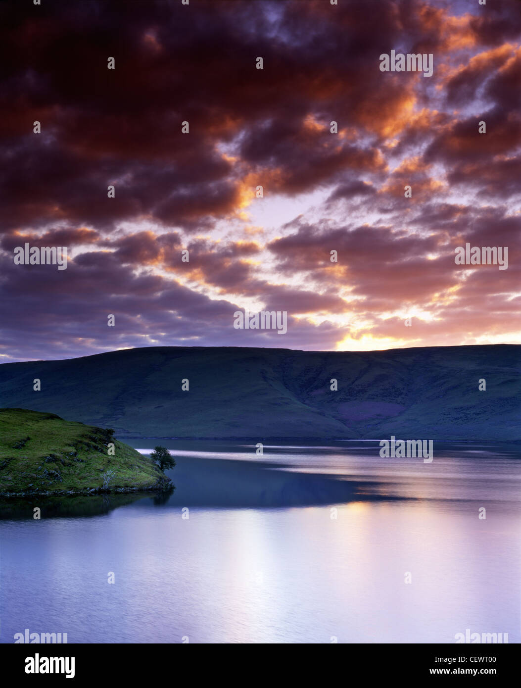 Heavy clouds part as dawn breaks over Penygarreg Reservoir in the Elan Valley. - Stock Image