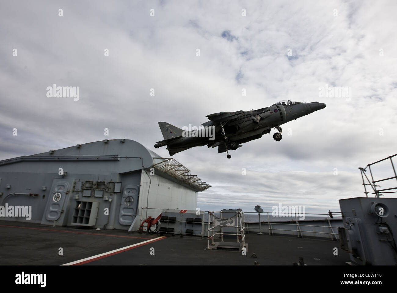 Harrier jet taking off from naval aircraft carrier HMS Illustrius - Stock Image