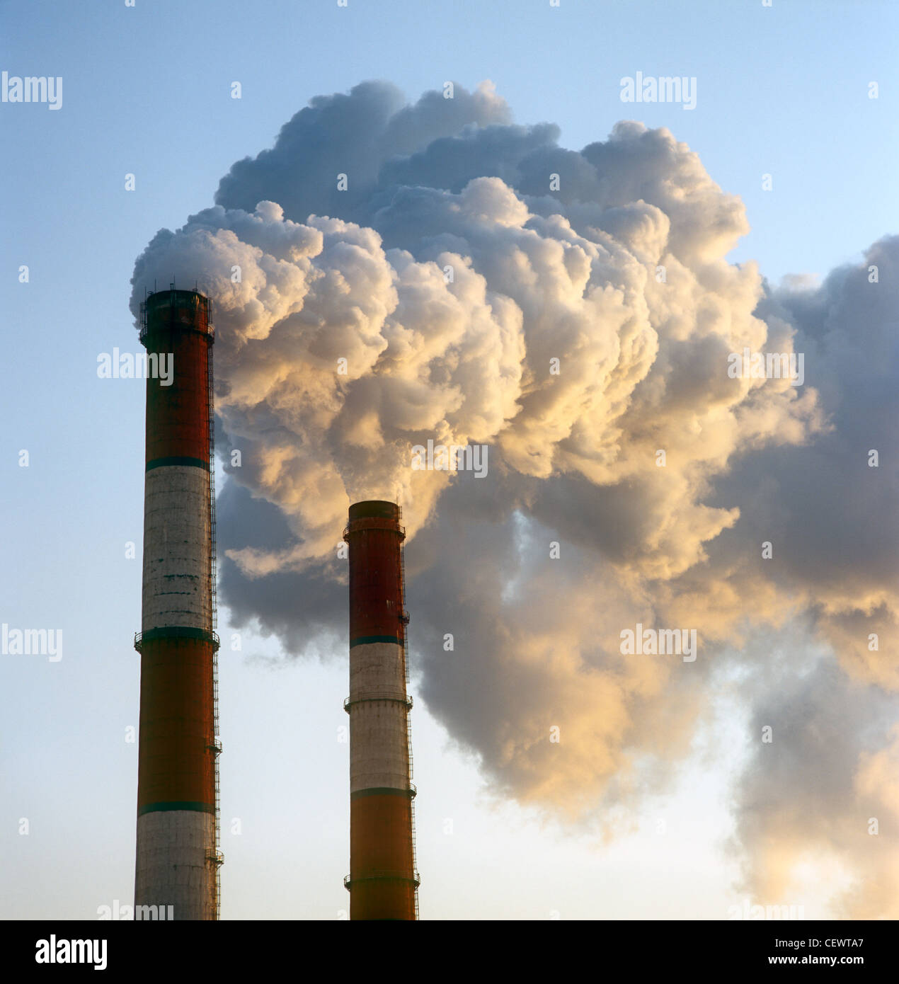 Air pollution by smoke coming out of two factory chimneys. - Stock Image