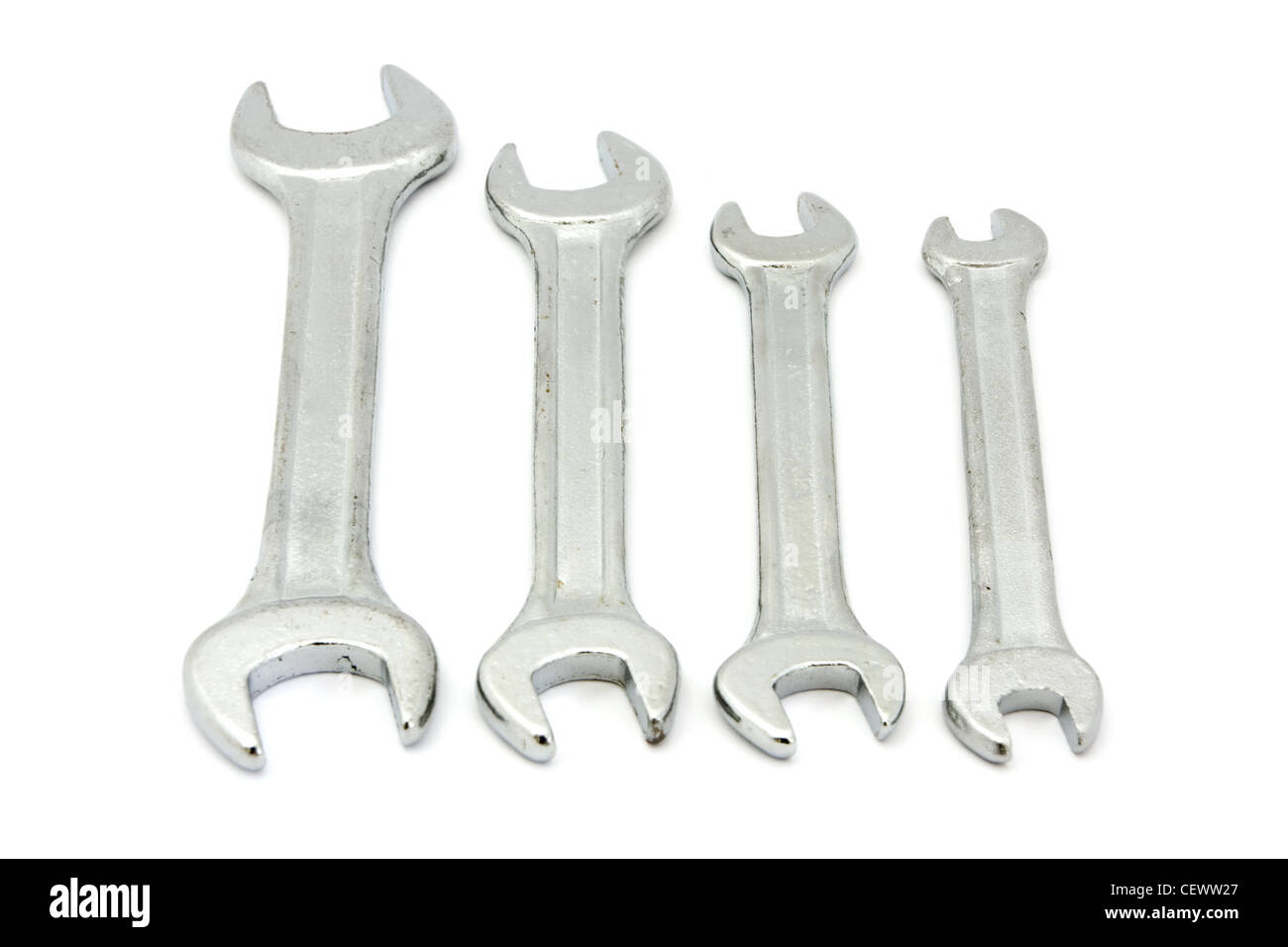 Line of four spanners over white - Stock Image