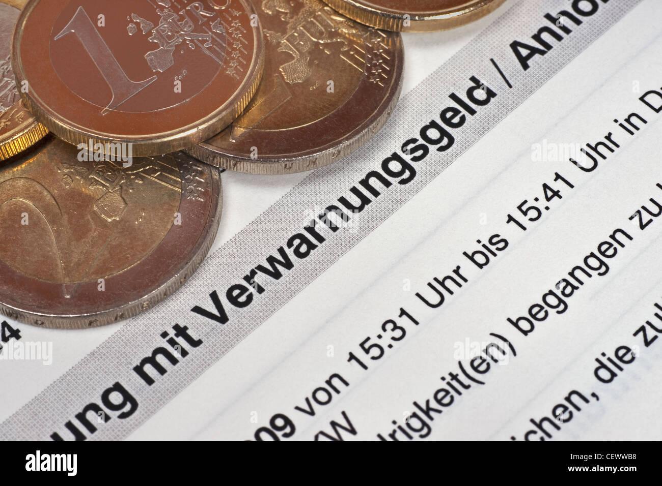 Verwarnungsgeld, daneben liegen einige Euro Münzen   fine for speeding, some Euro coins alongside - Stock Image