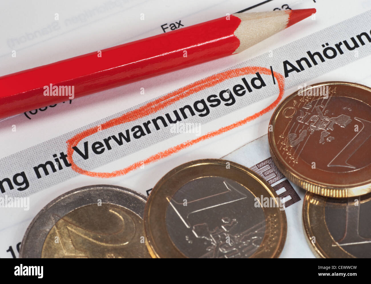 fine for speeding, marked red, beside is a red colored crayon and some Euro coins - Stock Image