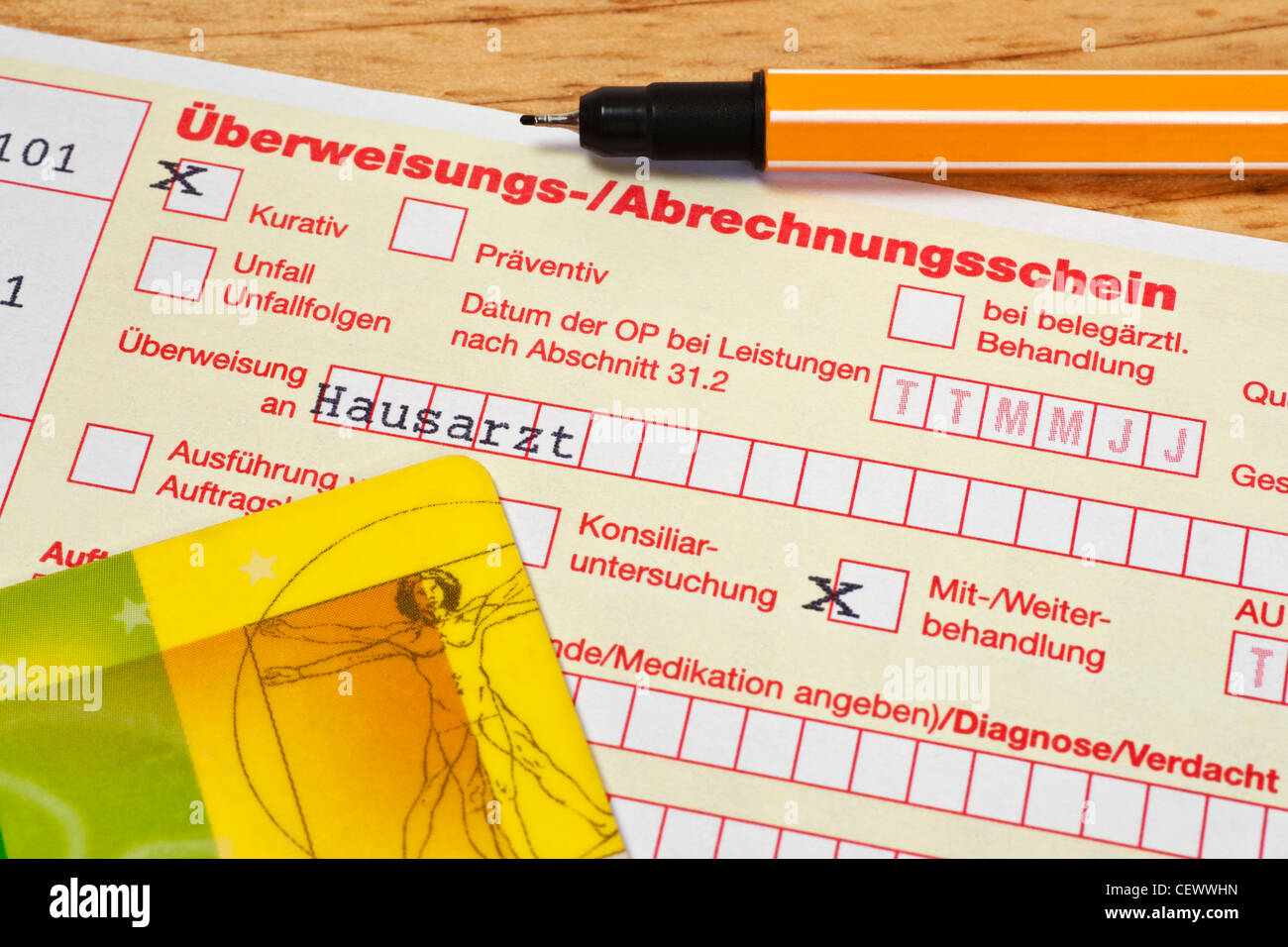 Detail photo of a German letter of referral to general practitioner, a pen and a health insurance card are alongside - Stock Image