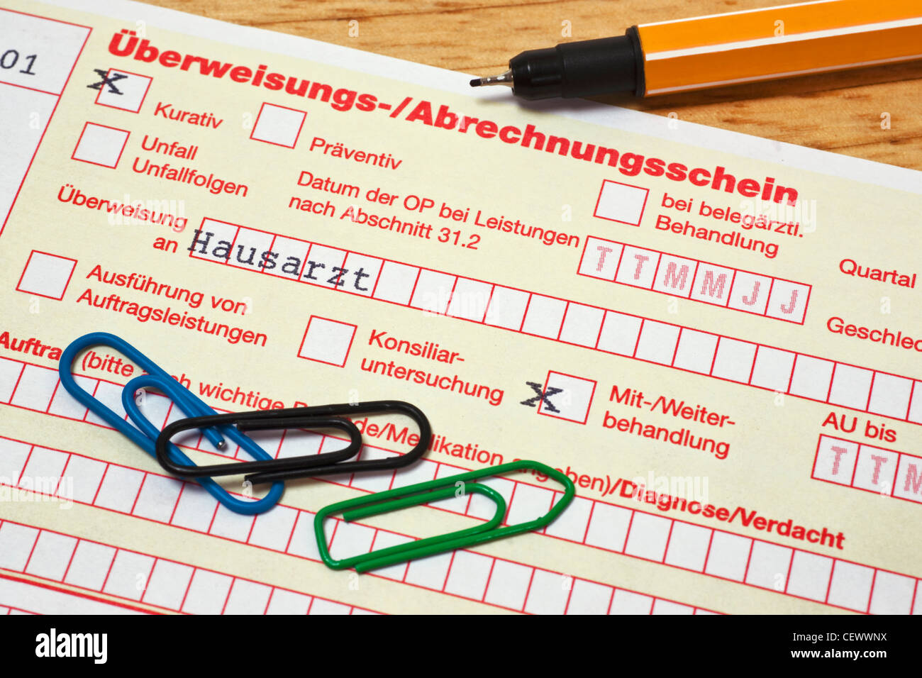 Detail photo of a German letter of referral to general practitioner, a pen and paper clips are alongside - Stock Image