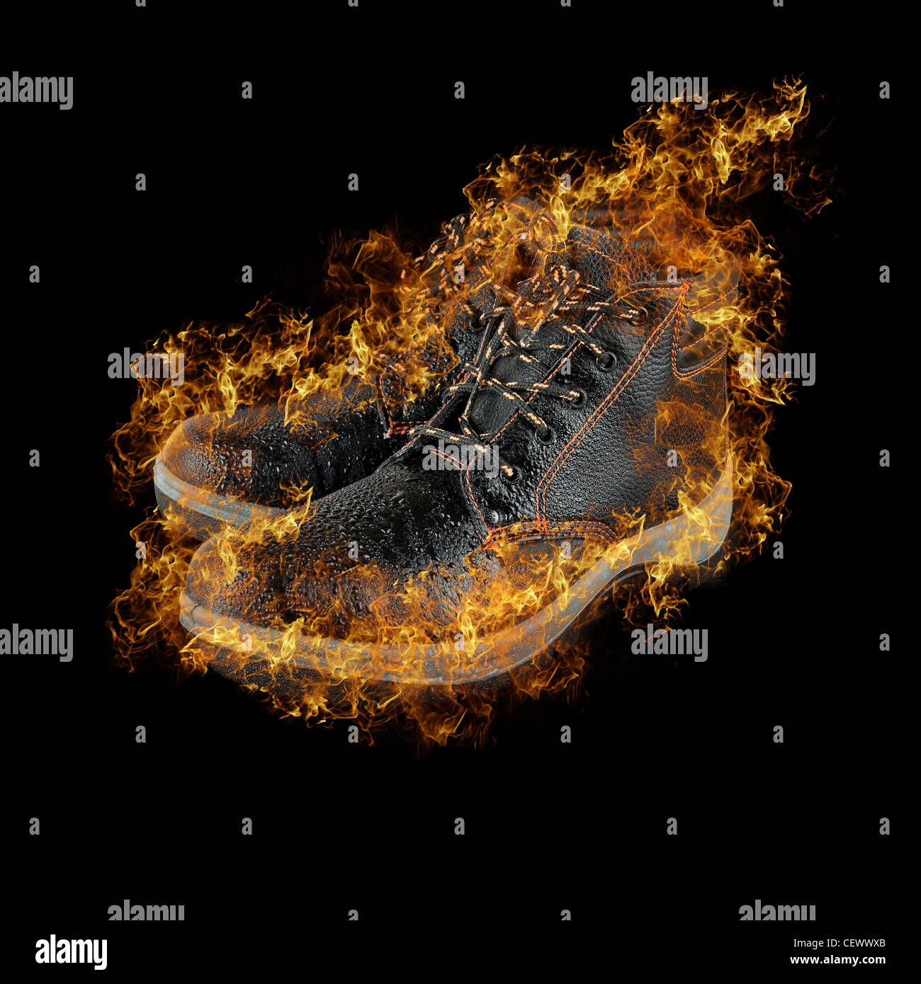 moist modern working boots at fire isolated on a black background - Stock Image