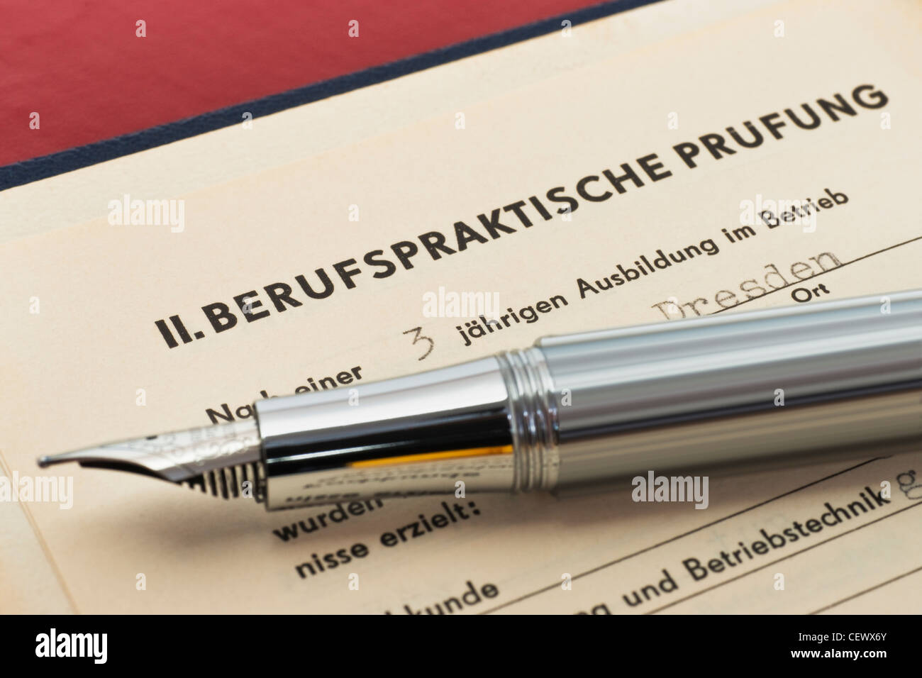 GDR craft certificate from 1954, the page of the work practical test is opened, a fountain pen is alongside - Stock Image