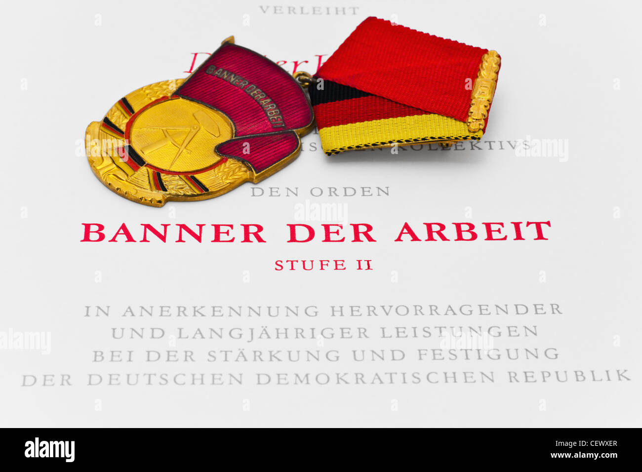 Partial view of a deed and the decoration Banner of Labor second class from GDR - Stock Image