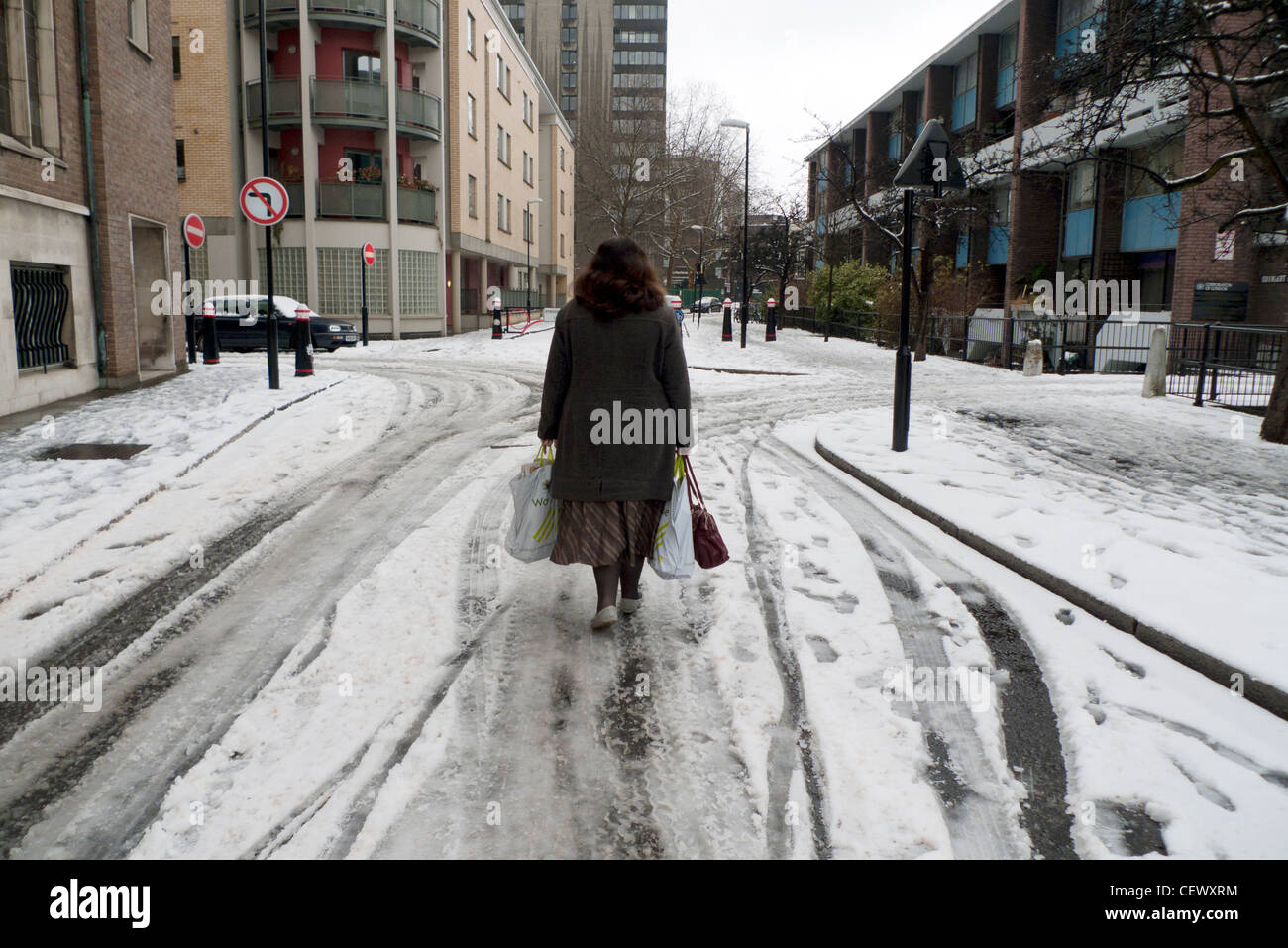 A woman walking along a snowy street in winter wearing shoes with Waitrose shopping bags near Golden Lane in Central Stock Photo