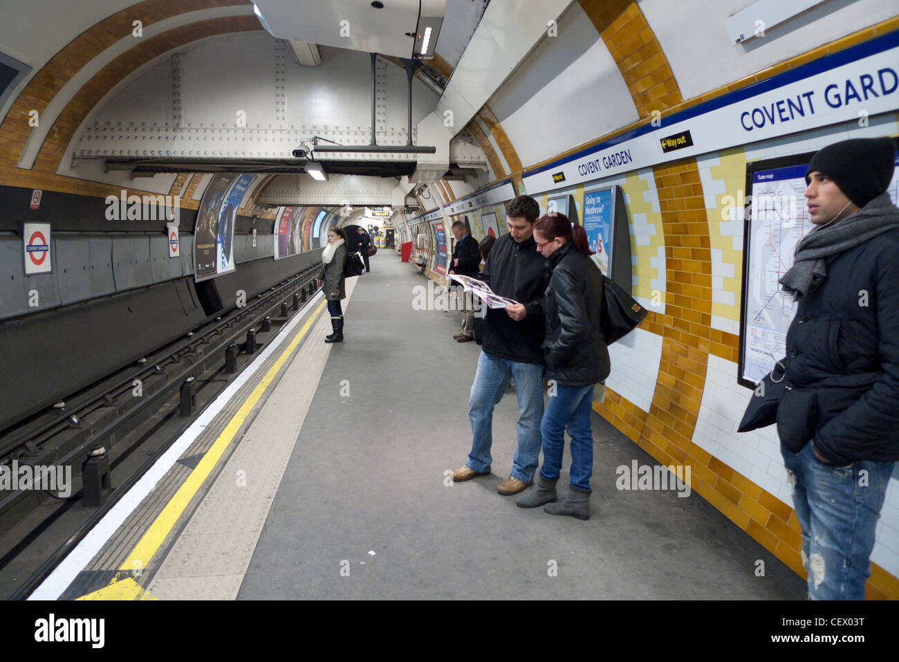 Passengers waiting for underground train on the Piccadilly line platform at Covent Garden Station London England - Stock Image