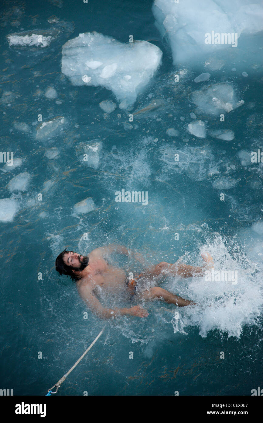 Guide taking Arctic plunge among ice-floes, Svalbard , Norway - Stock Image