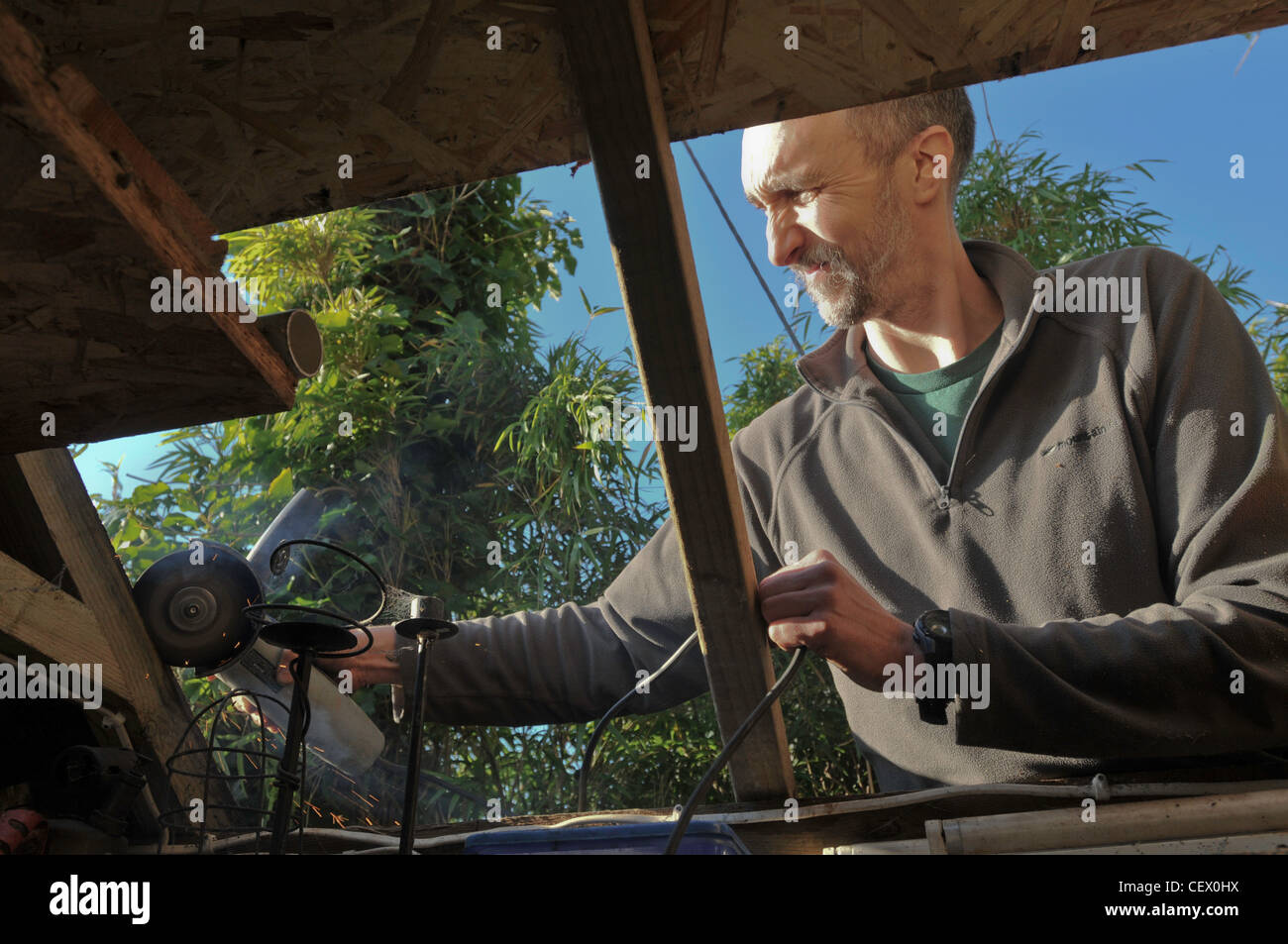 A man repairing the roof of his shed using a power tool - Stock Image