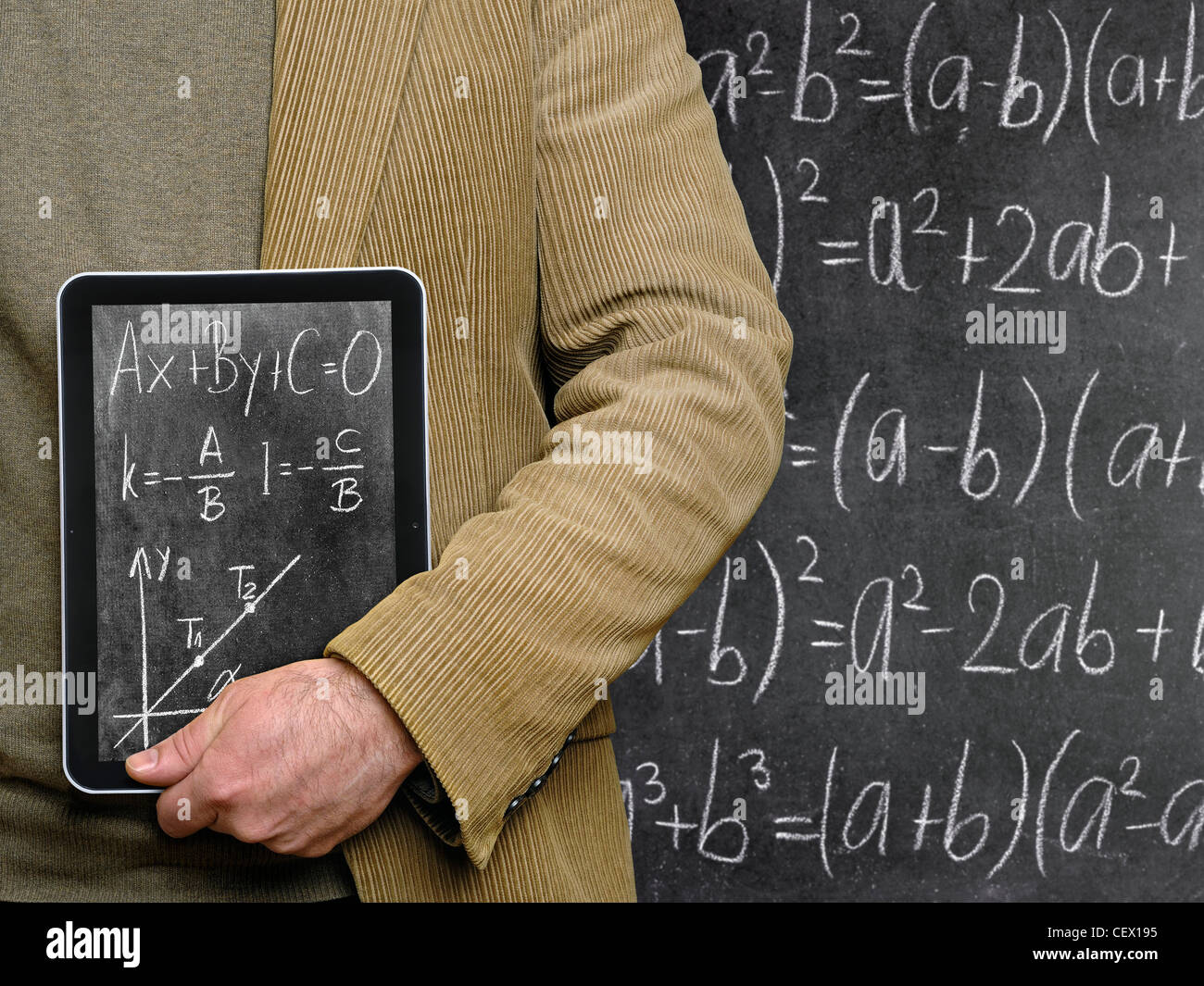 Teacher Holding a Tablet Computer in Front of a Chalkboard. - Stock Image