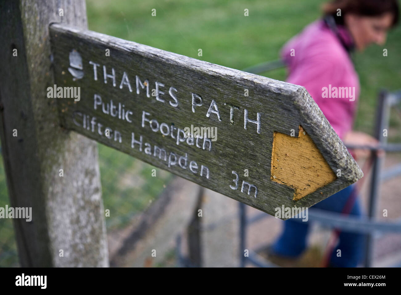 A walker with her dog passing through a gate beneath a signpost on the Thames Path showing the direction and mileage - Stock Image