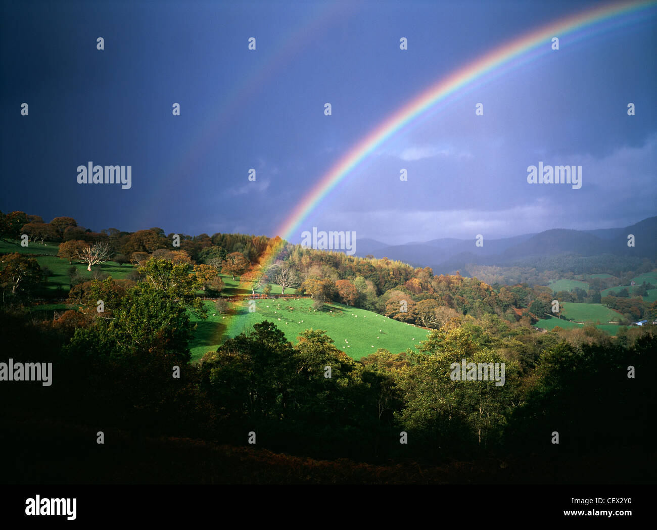 Storm light with rainbow against dark skies over Welsh hills. - Stock Image