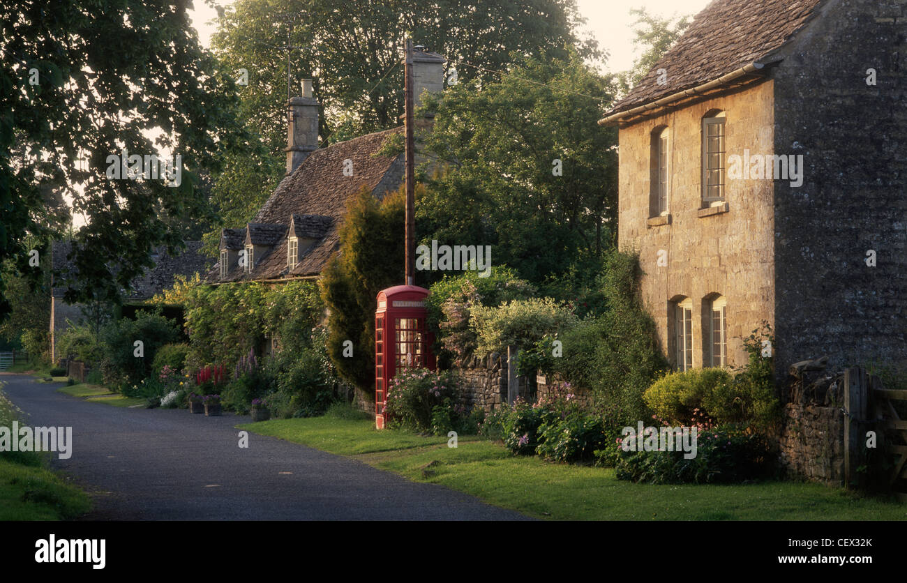 Old fashioned red phone box and village houses in the Cotswold village of Taynton. - Stock Image